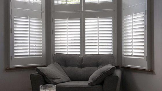 shuttersy w salonie na oknie z wykuszem