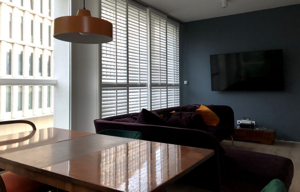 shuttersy w salonie, białe okiennice wewnętrzne