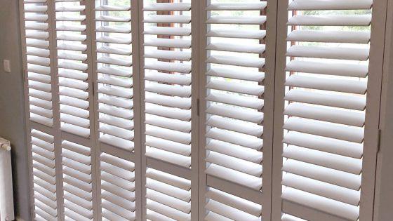 białe okiennice wewnętrzne, shuttersy w pokoju dziennym
