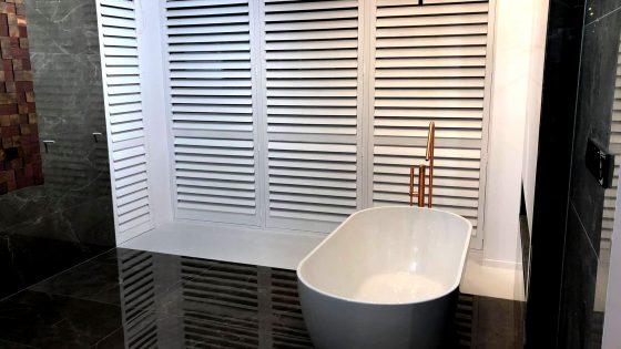 shuttersy w łazience, aranżacja z białymi okiennicami wewnętrznymi