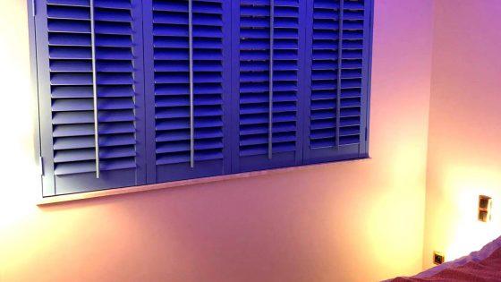 niebieskie shuttersy w sypialni z podświetleniem