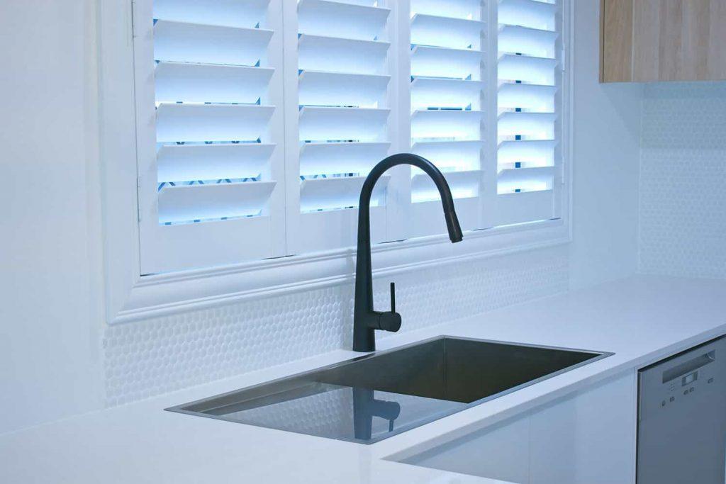 Odporne na wilgoć okiennice wewnętrzne shutters nad zlewozmywakiem w kuchni
