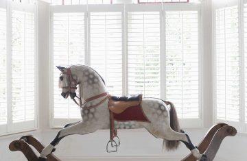 Konik na biegunach w pokoju dla dziecka z oknem wykuszowym