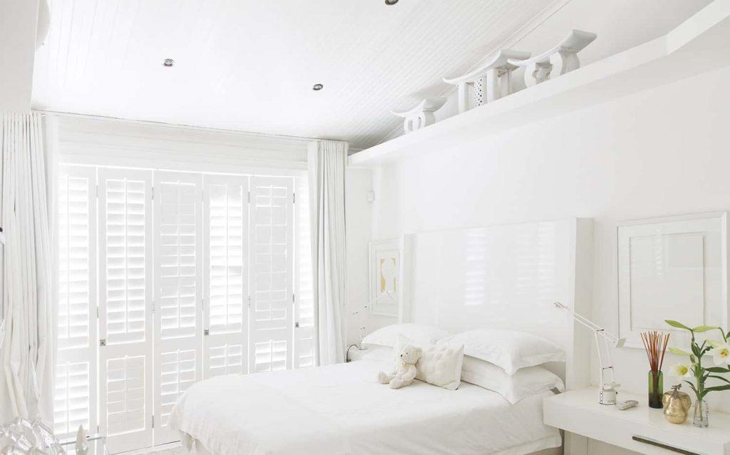Jasna sypialnia z białymi shuttersami