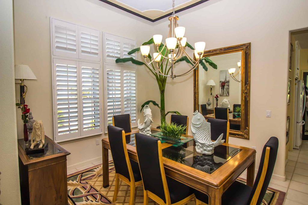 Białe shuttersy idealnie dopełniają wystrój eleganckiej jadalni z elementami czerni i złota