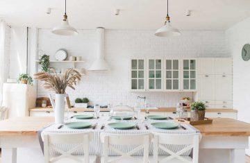 Biała kuchnia urządzona w stylu hygge - minimalistyczne wnętrze wykończone drewnem