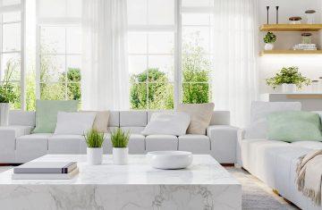 Nowoczesna kuchnia i nowoczesny salon w białej aranżacji - duże okna osłonięte są lekkimi firankami